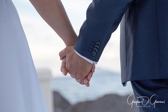 Matrimonio a Salina. lingua, dettaglio sposi mano nella mano