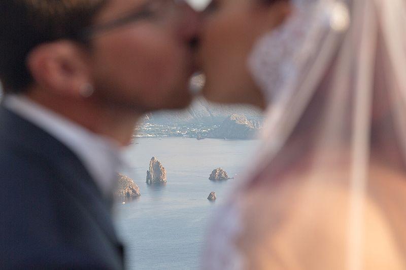 faraglioni lipari e vulcano sullo sfondo con sposi che si baciano