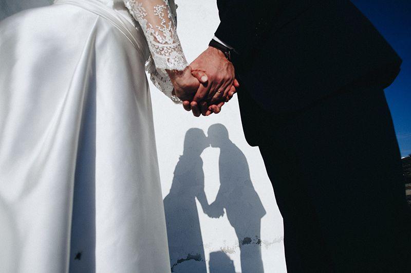 sposi mano nella mano con bacio ombre