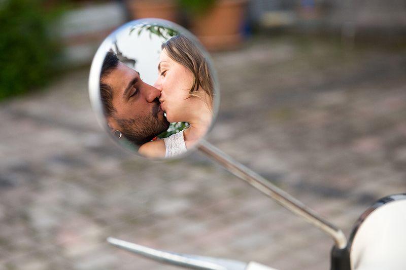 sposi si baciano riflessi nello specchietto della vespa