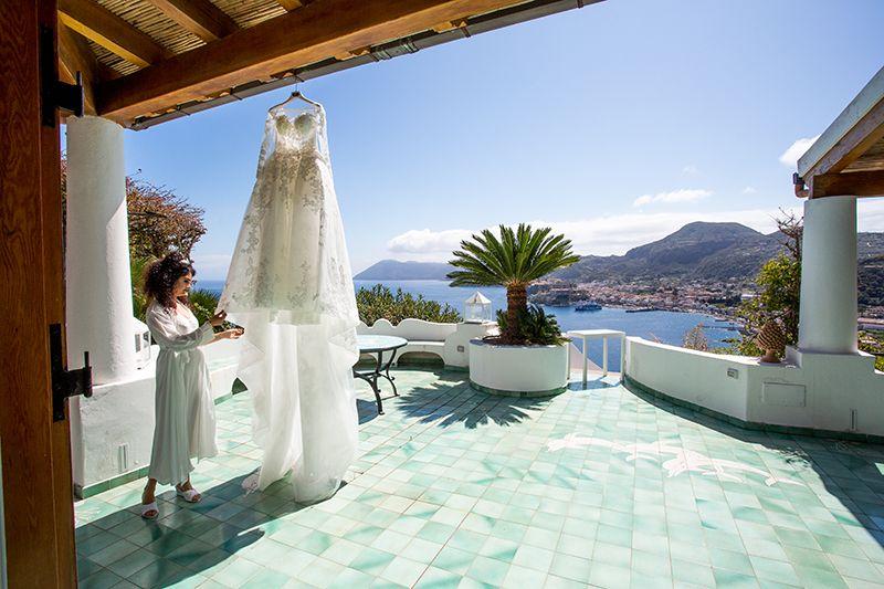 sposa guarda abito con lipari e vulcano come panorama