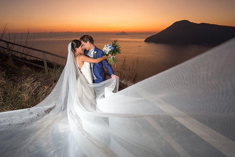 sposi al tramonto con salina filicudi sullo sfondo